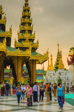 AS06IHO0844 Myanmar. Yangon. Shwedagon Pagoda. Visitors walk through the complex in late afternoon light.