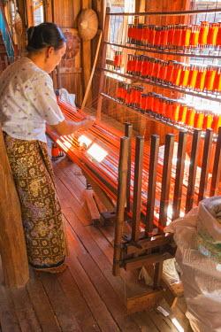 AS06IHO0952 Myanmar. Shan State. Inle Lake. Ko Than Hlaing silk and lotus weaving center. Woman weaving silk at a wooden loom.