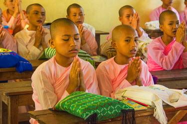 AS06IHO0972 Myanmar. Mandalay. Sagaing Hill. Aung Myae Oo Monastic Education School. Young Buddhist nuns pray before the start of class.