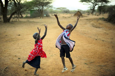 AF21AAS0052 Kenya, Laikipia, Il Ngwesi, playing and running girl after bubbles