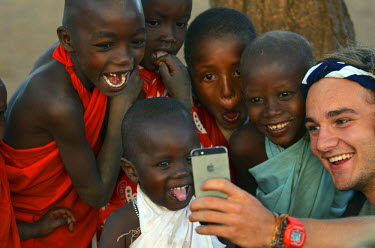 AF21AAS0068 Kenya, Laikipia, Il Ngwesi, young adult tourist taking selfie with local Masai children