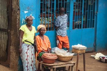 AF40ALA0004 Africa, Sierra Leone, Freetown. Women selling food on the sidewalk.