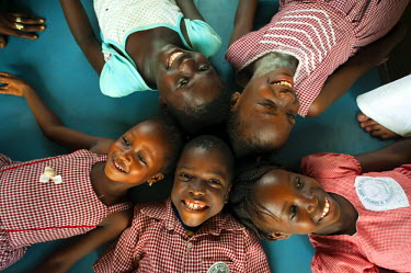 AF20AAS0027 Cote d'Ivoire, Abidjan, smiling black children lying on table in star shape (MR)