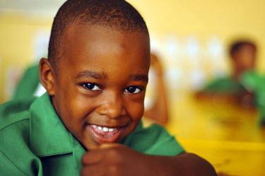 CA13AAS0021 Dominica, Roseau, Preschool Social Center, smiling boy at yellow school table