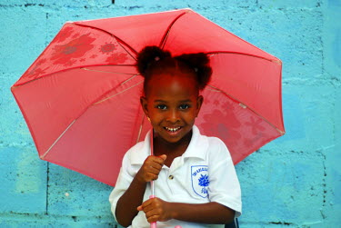 CA13SRA0034 Dominica, Roseau, Preschool CCF, young girl playing with pink umbrella against blue wall