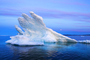 CN15PSO0002 Canada, Nunavut Territory, Moon rises behind melting iceberg in Frozen Channel at northern edge of Hudson Bay near Arctic Circle