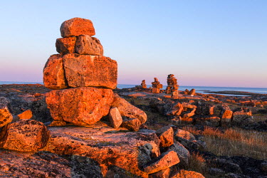 CN15PSO0023 Canada, Nunavut, Territory, Setting sun lights stone cairn and wooden cross on Harbor Islands along Hudson Bay near Arctic Circle