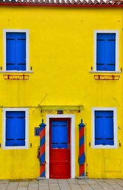 EU16DGU0002 Shuttered blue windows with bright yellow building Burano, Italy
