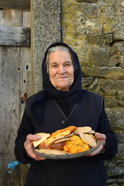 POR8651AW Mrs. Maria Claudina offers cakes to everybody during the traditional Winter festivities in Constantim. Tras-os-Montes, Portugal