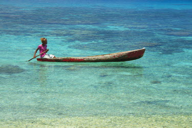 OC04CMI0036 Melanesia, Solomon Islands, Santa Cruz Island group, Malo Island. Clear shallow bay and coral reef, village girl in typical wooden dugout canoe.
