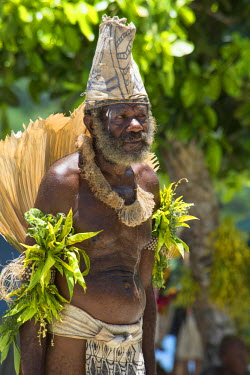 OC04CMI0095 Melanesia, Solomon Islands, Santa Cruz Island group, Malo Island. Village elder in native tapa cloth headdress and palm leaf attire performing traditional folkloric dance.