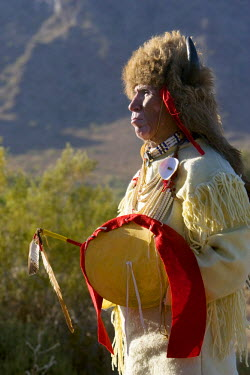 US03AWY0199 Native American man of the Sioux Nation dressed in traditional regalia and bison headdress holds a medicine stick and shield. Arizona, USA (MR)