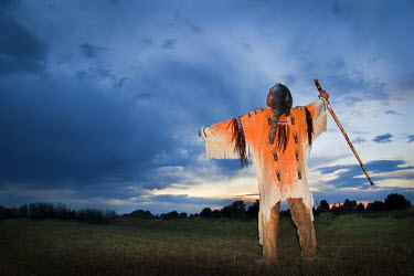 US13AWY0015 Back view of Native American medicine man dressed in ghost shirt holds wooden staff (MR) Idaho, USA