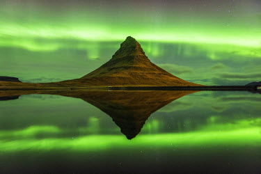ICE3543AW Grundafjordur, Snaefellsness peninsula, Western Iceland. Kirkjufell mountain reflecting in the waters of the lake with the northern lights (aurora borealis) in the background.