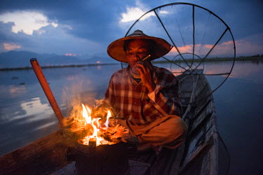 MYA2010AW Inle lake, Nyaungshwe township, Taunggyi district, Myanmar (Burma). Local fisherman before dawn with fireplace on the boat.