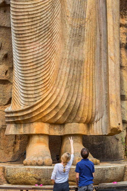 HMS1983554 Sri Lanka, North Central province, Kekirawa, Avukana temple, Buddha statue (abhaya-mudr position) in the 5th century carved directly into the granite hill 12 meters high, tourist couple in front of th...