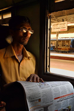 HMS2231955 Sri Lanka, Colombo, Colombo Fort train station, passenger reading a newspaper