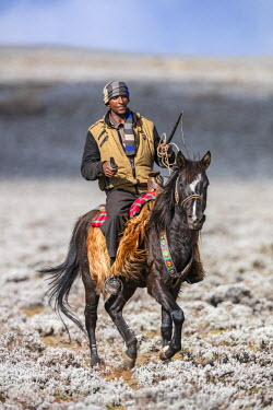 ETH2855 Ethiopia, Oromia Region, Bale Mountains, Bale National Park, Sanetti Plateau. An Ethiopian horsemen rides across the high-altitude, treeless Sanetti Plateau.