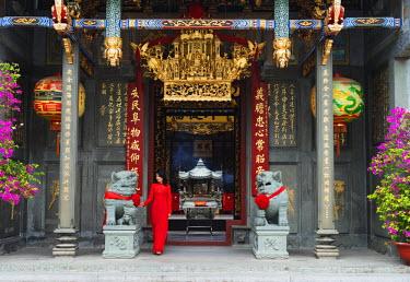 VIT0984 South East Asia, Vietnam, Ho Chi Mihn City (Saigon), Cholon, Nghia An Hoi Quan Pagoda, woman wearing aoi dai dress (MR)