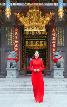 VIT0985 South East Asia, Vietnam, Ho Chi Mihn City (Saigon), Cholon, Nghia An Hoi Quan Pagoda, woman wearing aoi dai dress (MR)