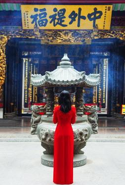 VIT0990 South East Asia, Vietnam, Ho Chi Mihn City (Saigon), Cholon, Nghia An Hoi Quan Pagoda, woman wearing aoi dai dress (MR)