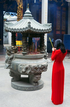 VIT0991 South East Asia, Vietnam, Ho Chi Mihn City (Saigon), Cholon, Nghia An Hoi Quan Pagoda, woman wearing aoi dai dress (MR)