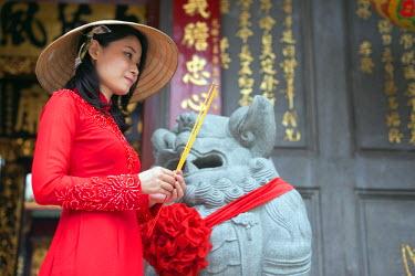 VIT0992 South East Asia, Vietnam, Ho Chi Mihn City (Saigon), Cholon, Nghia An Hoi Quan Pagoda, woman wearing aoi dai dress (MR)