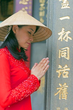 VIT0993 South East Asia, Vietnam, Ho Chi Mihn City (Saigon), Cholon, Nghia An Hoi Quan Pagoda, woman wearing aoi dai dress (MR)