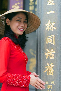 VIT0994 South East Asia, Vietnam, Ho Chi Mihn City (Saigon), Cholon, Nghia An Hoi Quan Pagoda, woman wearing aoi dai dress (MR)