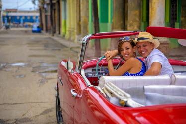 CB01755 Cuba, Havana, La Habana Vieja, Tourists enjoying 1950's classic American Buick (MR)