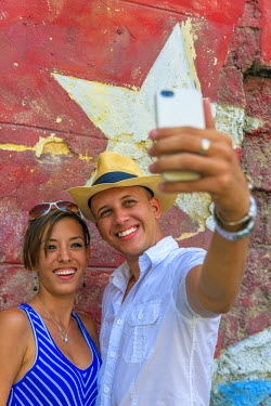 CB01764 Cuba, Havana, Tourist couple taking a selfie in front of mural