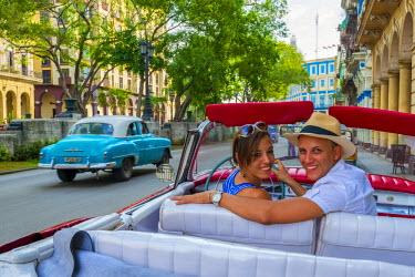 CB01771 Cuba, Havana, La Habana Vieja, Tourists enjoying 1950's classic American Buick (MR)