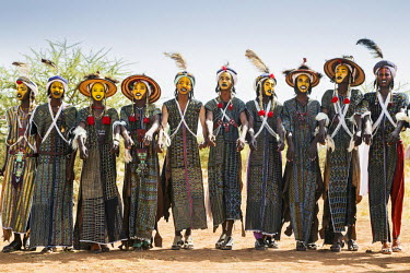 NIG7376 Niger, Agadez, Inebeizguine. Young Wodaabe men in traditional embroidered garments participate in the yakee dance known as the Dance of the Eyes.
