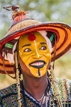 NIG7391 Niger, Agadez, Inebeizguine. A young Wodaabe man in traditional embroidered garments participates in the yakee dance known as the Dance of the Eyes.