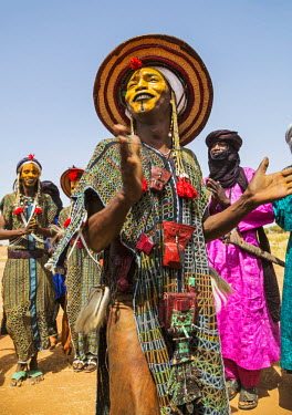 NIG7398 Niger, Agadez, Inebeizguine. Young Wodaabe men in traditional embroidered garments perform the rumi dance during a Gerewol ceremony.