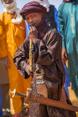 NIG7404 Niger, Agadez, Inebeizguine. A young Wodaabe boy wearing a sword in colourful matching attire.
