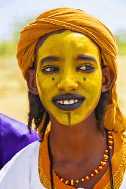 NIG7409 Niger, Agadez, Inebeizguine. A young Wodaabe man with a painted face during a Gerewol ceremony.