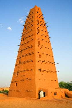 NIG7420 Niger, Agadez. The imam of the 16th century Agadez mosque beside the minaret which is claimed to be the tallest adobe structure in the world.