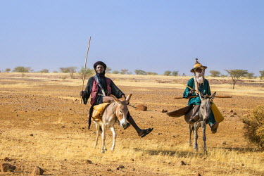 NIG7424 Niger, Agadez, Dabous. Two Wodaabe men ride on donkeys to a nearby well.
