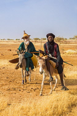 NIG7425 Niger, Agadez, Dabous. Two Wodaabe men ride on donkeys to a nearby well.