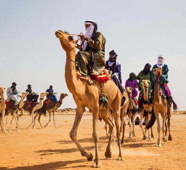 NIG7428 Niger, Agadez, Dabous. A group of Tuareg men in traditional dress ride their camels across desert terrain.