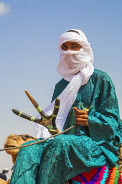 NIG7433 Niger, Agadez, Dabous. A Tuareg young man rides his camel sitting on a traditional three-pronged camel saddle.