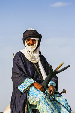 NIG7444 Niger, Agadez, Dabous. A Tuareg man sits on his camel using a traditional three-pronged camel saddle.
