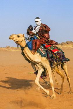 NIG7450 Niger, Agadez, Dabous. Two Tuareg men in traditional dress ride their camels at speed across desert terrain.