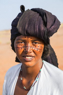 NIG7451 Niger, Agadez, Dabous. A Tuareg woman with painted patterns on her face. Her head scarf is coloured with indigo-blue.