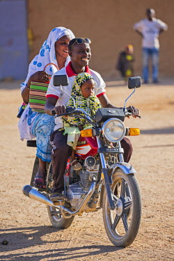 NIG7476 Niger, Agadez, Iferouane. A Tuareg family ride on their motor cycle.