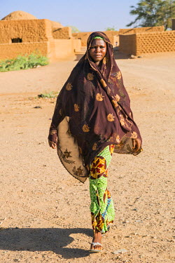NIG7477 Niger, Agadez, Iferouane. A girl walks through Iferouane town.