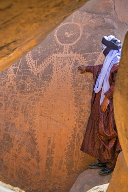 NIG7480 Niger, Agadez, Tirreghamis. A Tuareg admires a larger than life-size ancient hunter-gatherer rock engraving of a human male figure 3,000-4,000 years old.