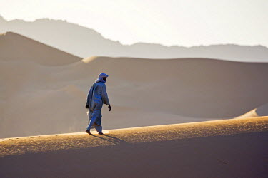 NIG7512 Niger, Agadez, Sahara Desert, Tenere, Kogo. A Tuareg walks up the ridge of a large sand dune in the Tenere with the Taghmert Mountains in the distance.