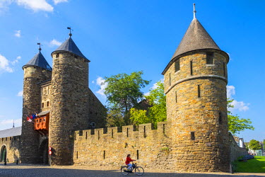 NLD0052AW A cyclist passes in front of Helpoort, old city gate and towers, Maastricht, Limburg, Netherlands